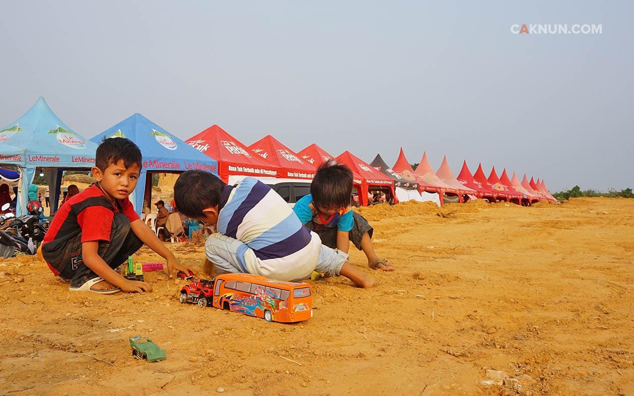 Anak-anak yang ceria bermain di tanah kosong. Foto: Acang.